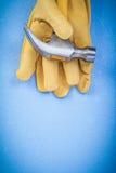 Vista verticale dei guanti di sicurezza del cuoio del martello da carpentiere su backg blu Immagini Stock Libere da Diritti