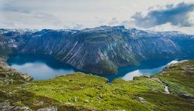 Vista vibrante di bella estate sul posto turistico norvegese famoso - trolltunga, la lingua dei troll con un lago e montagne, Nor fotografia stock