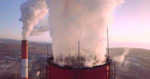 Vista vicina cima di camino della centrale elettrica e del riscaldamento centrale con vapore albeggiare stock footage