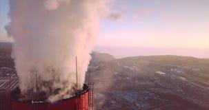 Vista vicina cima di camino della centrale elettrica e del riscaldamento centrale con vapore albeggiare video d archivio