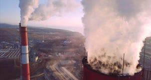 Vista vicina cima di camino della centrale elettrica e del riscaldamento centrale con vapore albeggiare archivi video