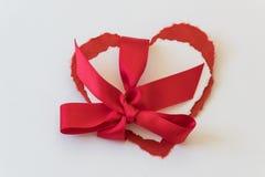 Vista vicina dei cuori del biglietto di S. Valentino del Libro rosso e Bianco legati insieme all'arco rosso del raso Fotografie Stock Libere da Diritti