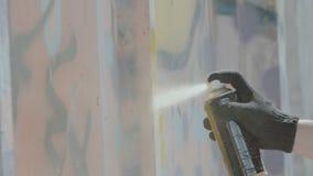 Vista vicina della mano in guanti neri che disegnano i graffiti sulla parete con il pallone video d archivio