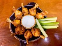 Vista vicina delle ali di pollo, dei bastoni di sedano e della besciamella in un piatto immagini stock