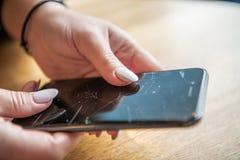 Vista vicina delle mani della donna con un telefono cellulare nero di cui lo schermo è rotto immagini stock