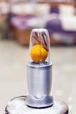 Vista vicina di un miscelatore con un'arancia ed i bastoni di cannella sulla a Fotografia Stock Libera da Diritti