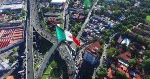 vista Zangão-aérea de uma bandeira mexicana enorme que vibra, apenas parte externa Cidade do México Uma estrada e alguns subúrbio