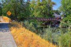 Vistas da ponte da trilha de Jordan River Trail Pedestrian e do trem com árvores circunvizinhas, azeitona de russo, cottonwood e  foto de stock