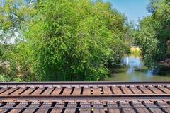 Vistas da ponte da trilha de Jordan River Trail Pedestrian e do trem com árvores circunvizinhas, azeitona de russo, cottonwood e  imagem de stock royalty free