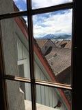Vistas de tejados y de Pilatus a través de la ventana foto de archivo libre de regalías
