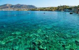 Vistas escénicas del fondo del mar con las piedras verdes, de una ciudad en la orilla y de un bote pequeño en la bahía de la isla imagenes de archivo
