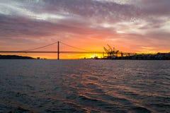 Vistas panorámicas del río Tagus, del puente 25 de abril Lisboa y del puerto en la puesta del sol de la nave, Portugal Fotos de archivo libres de regalías