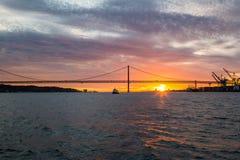 Vistas panorâmicas do Tagus River, da ponte o 25 de abril Lisboa e do porto no por do sol do navio, Portugal Imagens de Stock