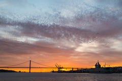 Vistas panorâmicas do Tagus River, da ponte o 25 de abril Lisboa e do porto no por do sol do navio, Portugal Imagem de Stock Royalty Free