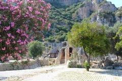 Vistas pitorescas das ruínas do teatro antigo no fundo das montanhas, árvores de florescência com flores roxas Fotos de Stock