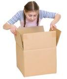 Vistazo de la muchacha en la caja de cartón Fotos de archivo libres de regalías