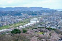 Viste dei fiori di ciliegia a Shiroishi RiversideHitome Senbonzakura o mille ciliegi a vista ed alla catena montuosa di Zao vedut Fotografia Stock