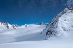 Viste innevate del ghiacciaio alpino sotto cielo blu dopo le precipitazioni nevose Fotografia Stock
