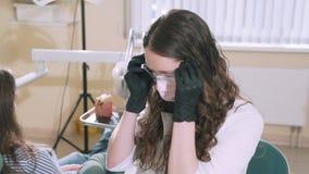 Visten al dentista a cámara lenta del doctor del steadicam del tiroteo del primer en su oficina en los guantes estéril, una másca almacen de metraje de vídeo