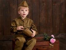 Visten al muchacho de los niños como soldado en uniformes militares retros con el frasco que se sienta en la maleta vieja, fondo  fotos de archivo libres de regalías