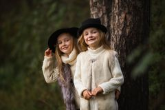 Visten a dos muchachas felices igualmente: en conferir y sombreros de la piel a las pequeñas novias del bosque en parque imágenes de archivo libres de regalías