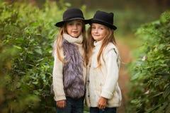 Visten a dos muchachas felices igualmente: en conferir y sombreros de la piel a las pequeñas novias del bosque en parque fotografía de archivo