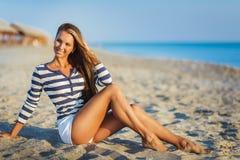 Visten a la mujer atractiva hermosa en un chaleco pelado mar se sienta en los sueños de la costa Foto de archivo libre de regalías