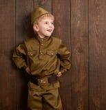 Visten a los niños como soldado en uniformes militares retros imagen de archivo libre de regalías
