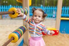 Visten a una niña con dos colas en una chaqueta colorida rayada está jugando en la salvadera en el patio fotografía de archivo libre de regalías