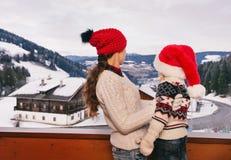 Visto da mãe de trás e da criança que olham montanhas neve-tampadas Fotografia de Stock