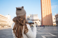 Visto da mulher de trás com a câmera retro na praça San Marco Foto de Stock