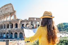 Visto de atrás, um turista da mulher que guarda um mapa em Colosseum Foto de Stock