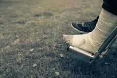 Visto desde arriba de pies en una silla de ruedas Pie con esguince en parte inferior de la hierba foto de archivo libre de regalías