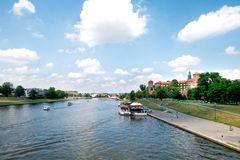 View down Vistula River in Krakow. Vistula River is occupied with sightseeing boats traveling along a castle on a sunny spring day in Krakow Poland stock image