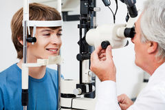 Visual Field Test For Glaucoma. Smiling boy getting visual field test done by the optometrist royalty free stock photography