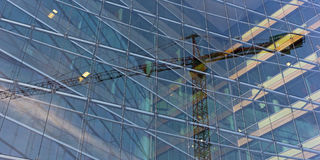 Visual illusion of constitution crane trapped inside the glass building. Stock Images