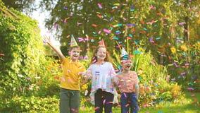 Visualización inversa para los niños felices en partido del carnaval debajo del confeti del vuelo almacen de metraje de vídeo