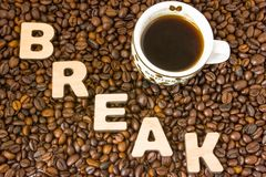Visualization of the concept or action Coffee Break. Word break, which is lined with large, 3D letters, lies in scattered roasted. Beans coffee near small mug Stock Photo