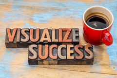Visualize success in wood type. Visualize success banner  - text in vintage letterpress wood type blocks stained by color inks against grunge wood with a cup of Stock Photos