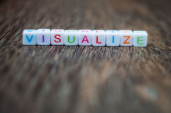 Visualize word on wood. Visualize word arranged from character cubes on wood table top. closeup. narrow depth of field Stock Photos