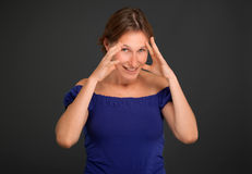Visualizing. Woman with her ands on her face visualizing something Stock Photography