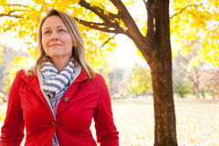 Visualizing Success and Retirement. An attractive woman out for a walk outside on a beautiful fall day wearing business casual attire including a red blazer and Royalty Free Stock Images