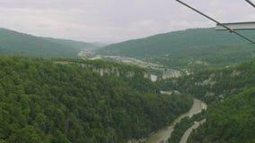 Visualizzazione dalla piattaforma d'esame del ponte sospeso del metallo alla valle verde della montagna con la strada ed il fiume archivi video