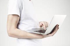 Visualizzazione del primo piano del computer portatile moderno in mani del ` s dell'uomo, maglietta bianca d'uso del tipo, lavora Fotografia Stock