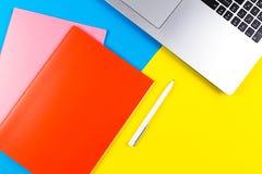 Visualizzazione superiore del computer portatile, dei taccuini di carta e della penna bianca sul fondo blu e giallo di colore Fotografia Stock Libera da Diritti