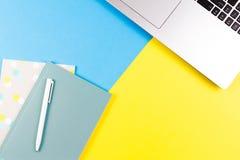Visualizzazione superiore del computer portatile, dei taccuini di carta e della penna bianca sul fondo blu e giallo di colore Immagine Stock
