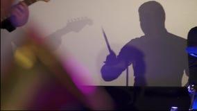 Visualizzi il chitarrista sulla parete bianca archivi video