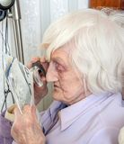 Visually impaired elderly woman with magnifyer royalty free stock photography