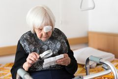 Visually impaired elderly 95 years old woman sitting at the bad trying to read with magnifying glass. Visually impaired elderly 95 years old woman sitting at Royalty Free Stock Photography