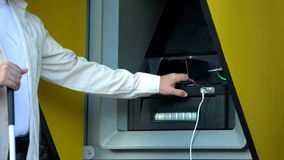 Visually impaired man inserting password on atm machine, withdrawing money